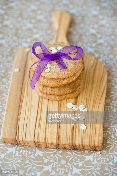 Stack of flapjacks tied with purple ribbon on wooden board and cloth