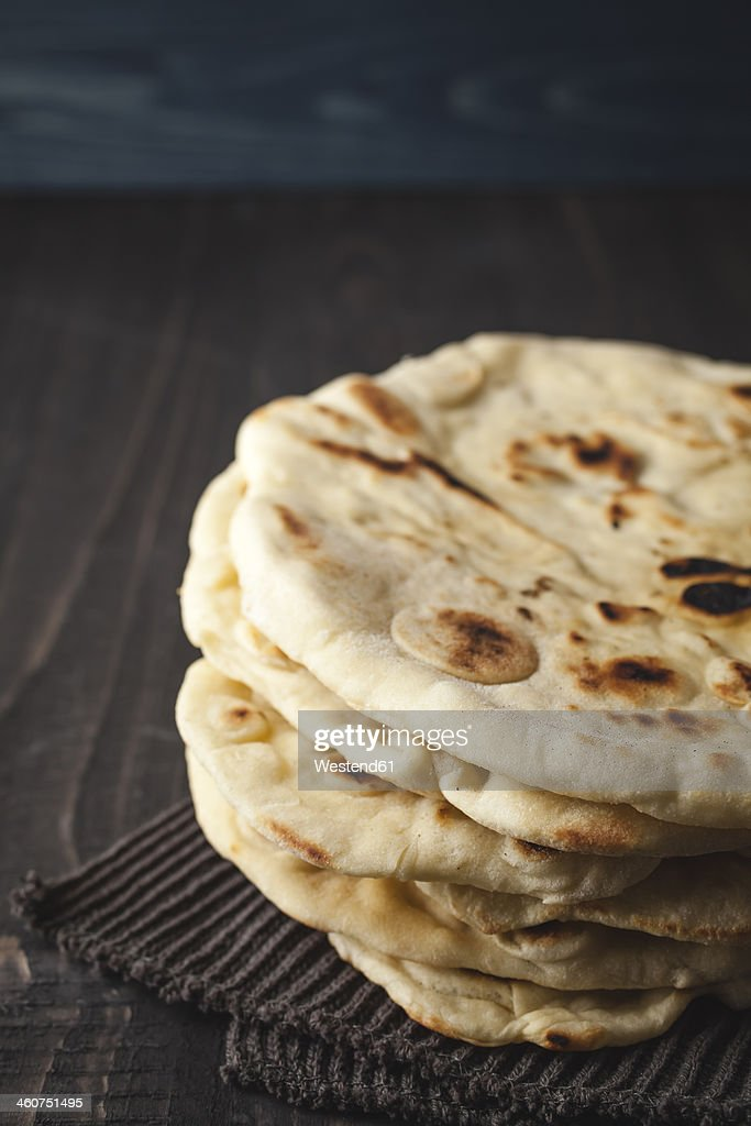 Stack of flat breads on wooden table, close up : Stock Photo