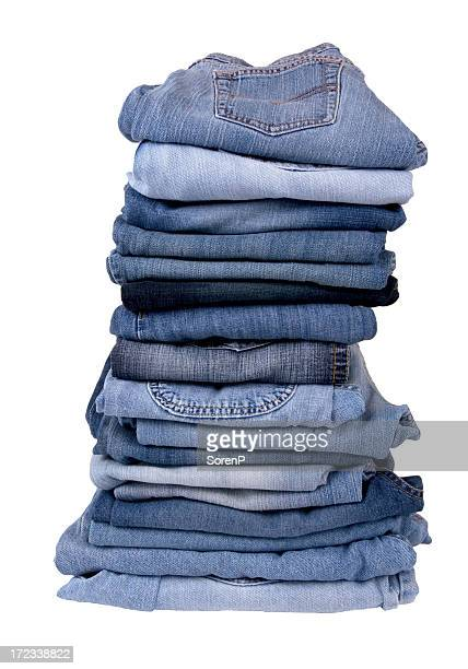 Stack of folded blue jeans on white background