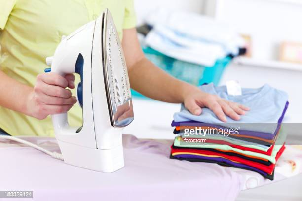 Stack of folded clean ironed clothes on an ironing board