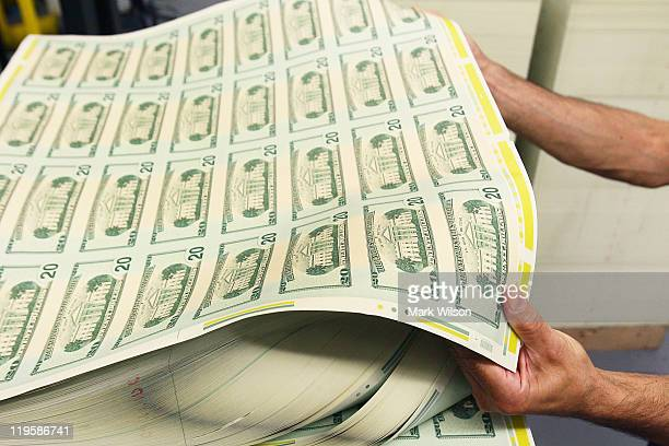 A stack of freshly made twenty dollar bills is inspected at the Bureau of Engraving and Printing on July 22 2011 in Washington DC The printing...
