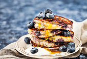 Stack of freshly prepared blueberry ricotta pancakes with fresh berries, yogurt and honey for breakfast