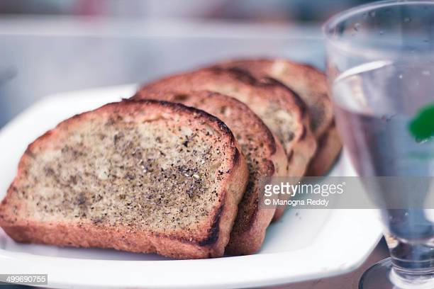 Stack of garlic bread with a glass of water