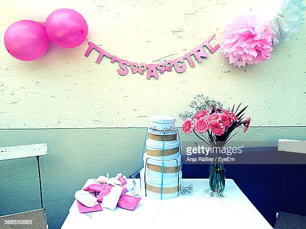 Stack Of Gifts By Vase On Table At Baby Shower