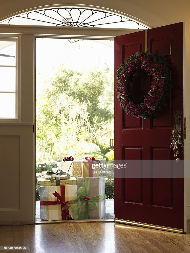 Stack of gifts outside front door : Stock Photo