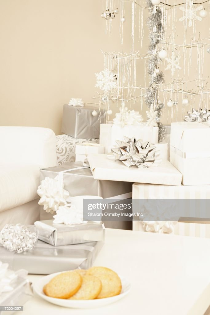 Stack of gifts under artificial Christmas tree : Stock Photo