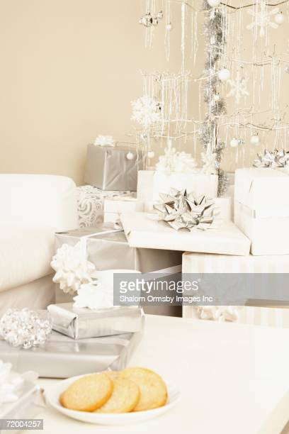Stack of gifts under artificial Christmas tree