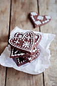 Stack of heart-shaped gingerbread decorated with sugar icing on paper