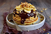 Stack of homemade delicious banana pancakes topped with chocolate sauce, banana slices and walnut on a plate on a dark wooden background.
