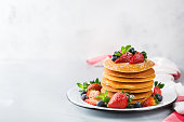 Food and drink, still life, healthy nutrition concept. Stack of homemade pancakes for breakfast with berries and sugar. Light copy space kitchen background