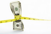 Measuring tape twining several US$100 bills over white background
