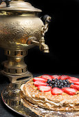 Thin pancakes cake from strawberry, blueberry and condensed milk in a metal plate and tea from a old gold samovar on the background. close-up