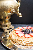 A stack of large pancakes cake from strawberry, blueberry and condensed milk in a metal plate and tea from a old gold samovar on the background. close-up