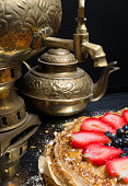 A stack of large pancakes cake from strawberry, blueberry and condensed milk in a metal plate and tea from a old gold samovar and pot of tea on the black background. close-up