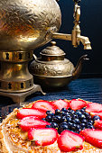 Large thin pancakes cake from strawberry, blueberry and condensed milk in a metal plate and tea from a old gold samovar and pot of tea on the black background. close-up