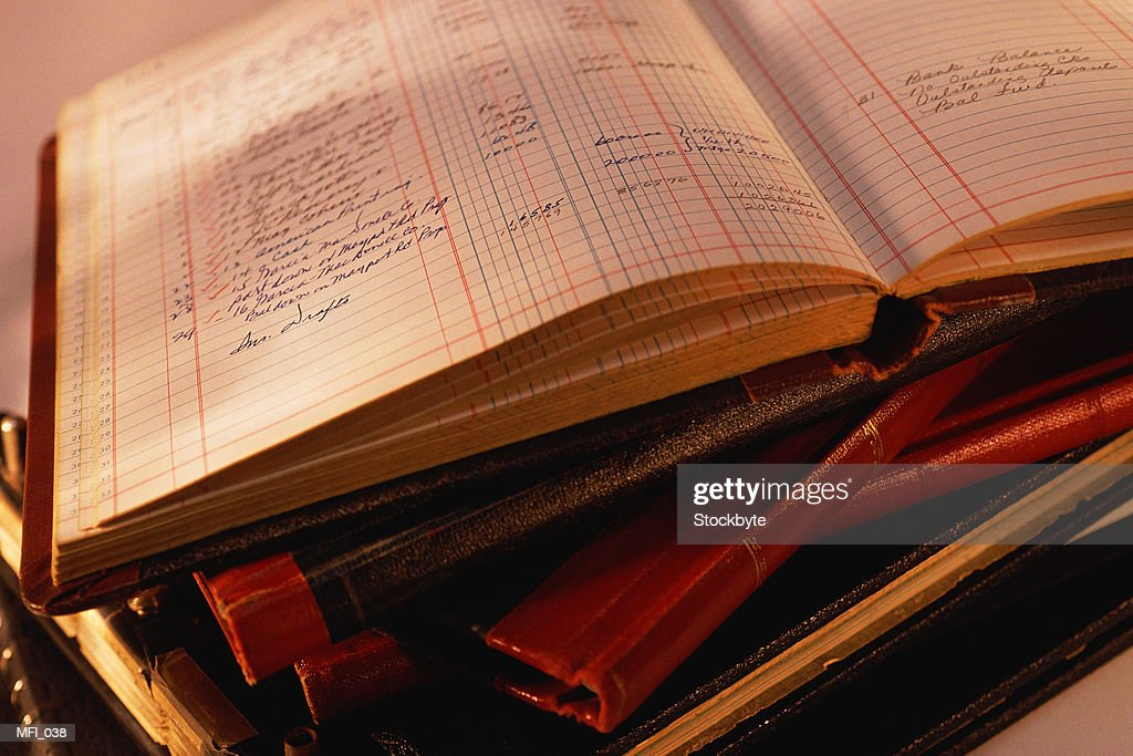 Stack of ledger books; top book open