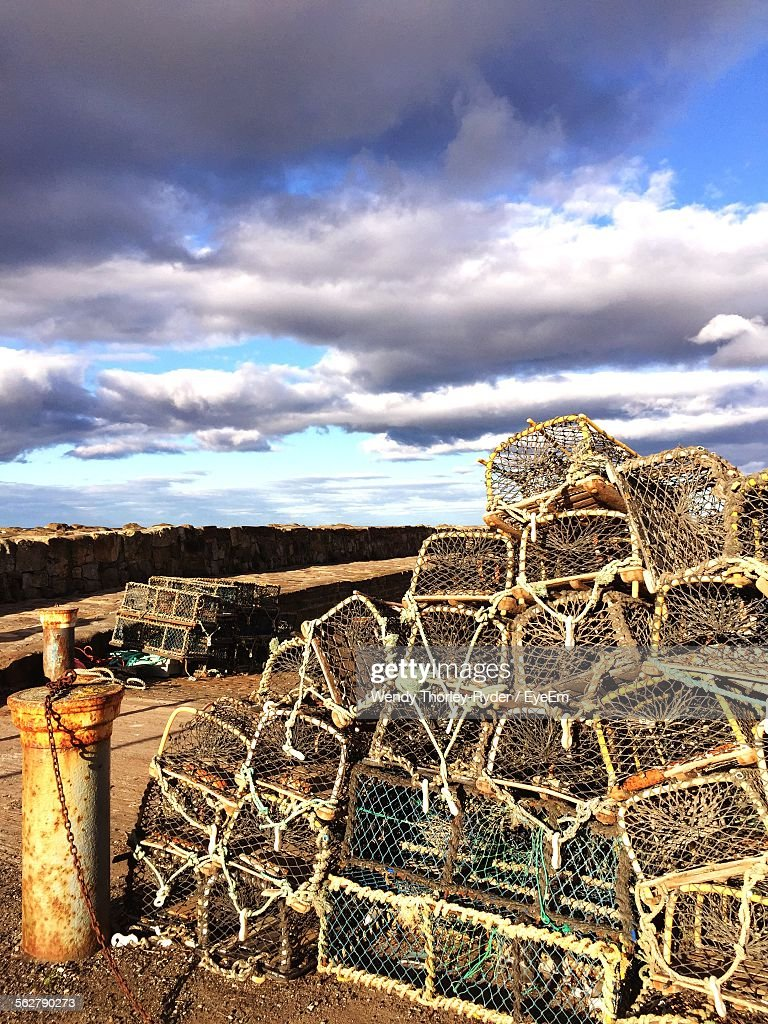 Stack Of Lobster Traps At Harbor Against Cloudy Sky