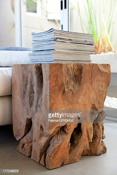 Stack of magazines on a table made from tree stump