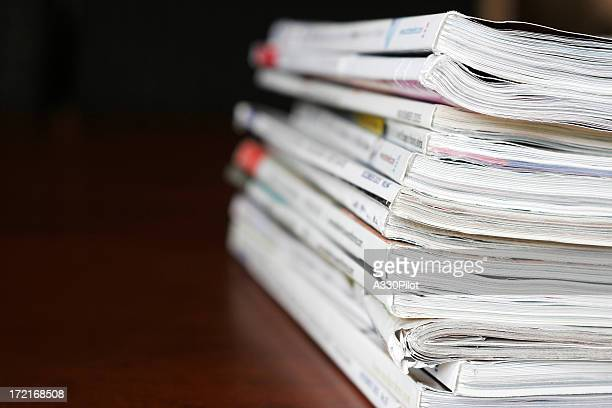 Stack of magazines over a wooden desk