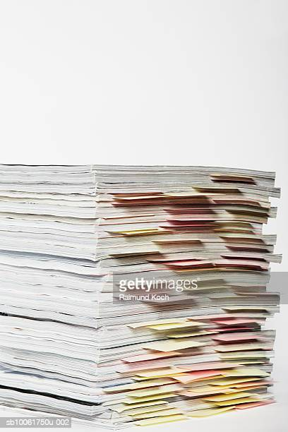 Stack of magazines with colored bookmarks, studio shot