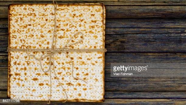 Stack of matzah or matza on a vintage wood background presented as a gift
