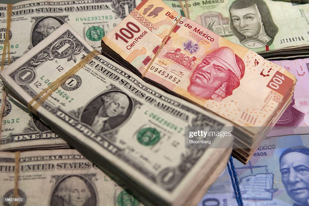 A stack of Mexican hundred peso bills and U.S. dollar bills are arranged for a photograph inside a currency exchange in Mexico City, Mexico, on Tuesday April 9, 2013. Mexico's peso rose to the strongest since August 2011 after a report showed faster-than-forecast inflation last month, damping speculation that policy makers will cut interest rates to slow the currency's advance. Photographer: Susana Gonzalez/Bloomberg via Getty Images