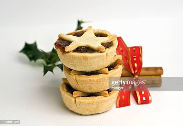 stack of mince pies with cinnamon and holly