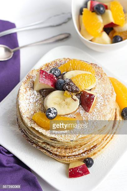 Stack of mini pancakes filled with chocolate cream and sliced fruits