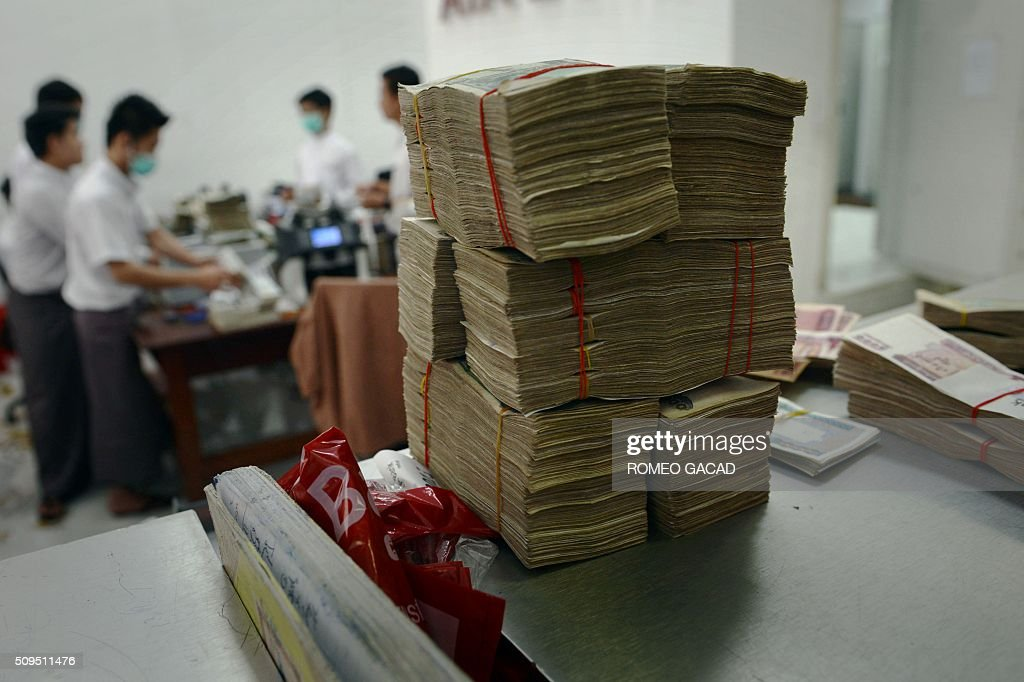A stack of Myanmar kyat banknotes sit stacked up on the counter at a bank in Yangon on February 11, 2016. An International Monetary Fund report last September indicated the Myanmar economy was expected to grow by 8.5 percent in 2015 and at a similar pace in 2016, fueled by the strong growth momentum and expansionary macroeconomic policies. AFP PHOTO / ROMEO GACAD GACAD
