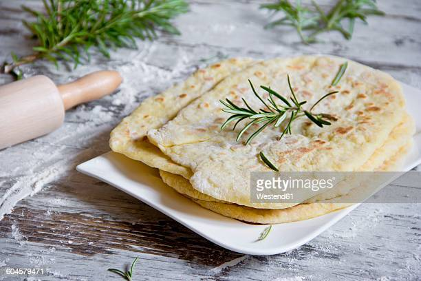 Stack of naan breads with rosemary twig on plate