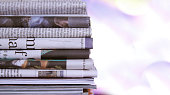 Some newspaper, stacked on bokeh background
