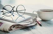 Stack of newspapers, eyeglasses on table