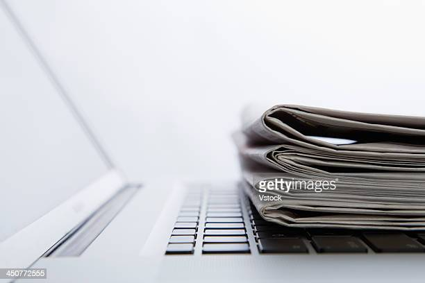 Stack of newspapers on laptop. close-up