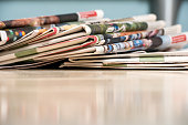 Stack of newspapers on white wood table