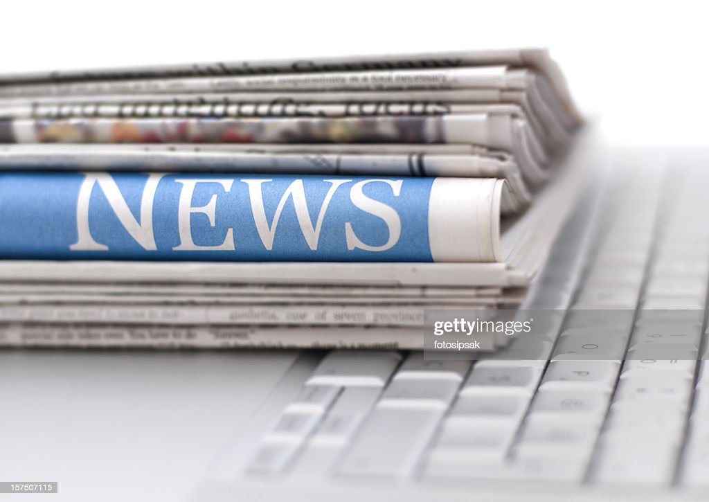 Stack of newspapers resting on laptop keyboard : Stock Photo