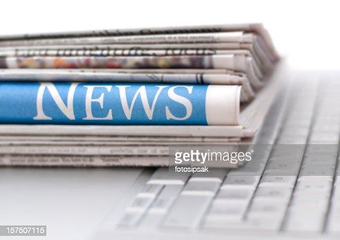 Pile de journaux sur un clavier d'ordinateur portable
