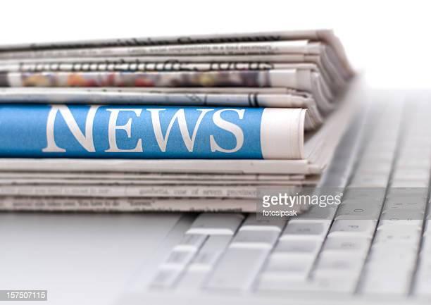 Stapel Zeitungen, die auf laptop Tastatur