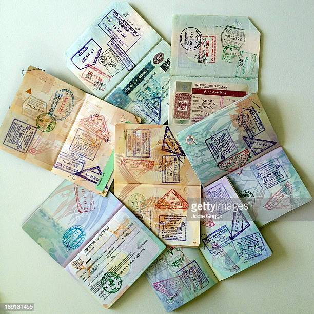 Stack of open passports with date stamps and visas