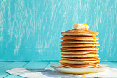 Stack of pancakes with honey and piece of butter on plate which stands on napkin on blue wooden table. Copyspace. Concept of shrovetide treats. Selective focus