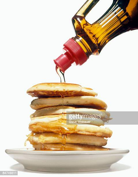 stack of pancakes on a plate with syrup pouring