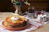 A stack of pancakes in a clay plate and a glass of tea from a samovar on the background of a log wall.