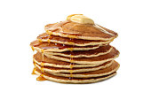Stack of pancakes with butter and a flowing maple syrup isolated on white