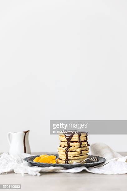 Stack of pancakes with chocolate sauce and slices of orange on a plate