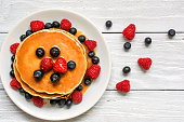 stack of pancakes with fresh berries and caramel sauce on white wooden background. top view