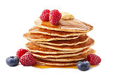 Stack of pancakes with maple syrup and fresh berries isolated on white background