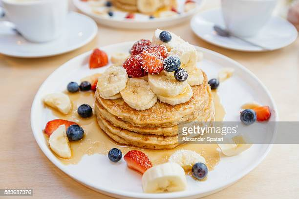 Stack of pancakes with maple syrup, banana, strawberry and blueberry on the plate