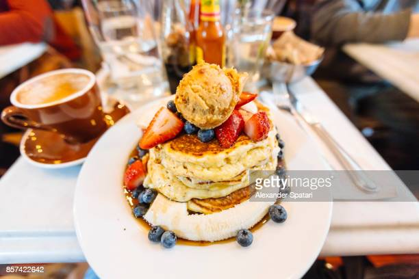 Stack of pancakes with maple syrup, banana, strawberry, blueberry and ice cream on the plate, personal perspective