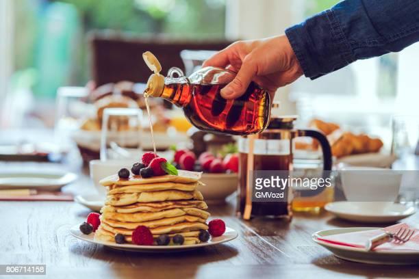 Stapel von Pfannkuchen mit Ahornsirup, Beeren und frischen Kaffee