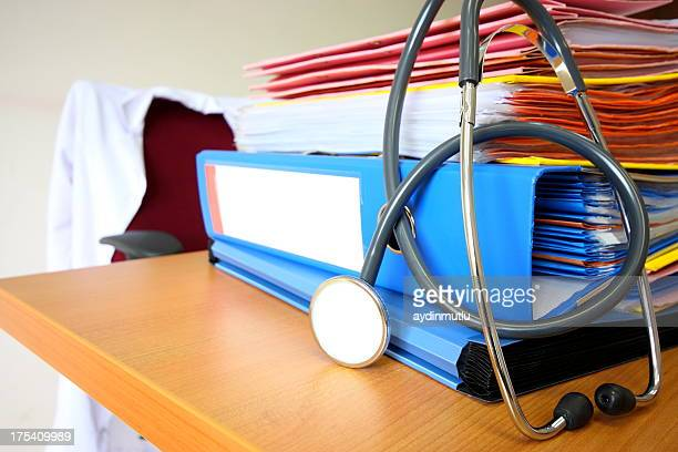 A stack of papers and a stethoscope on a desk