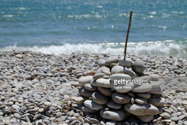 Stack Of Pebbles On Beach Against Blue Sea
